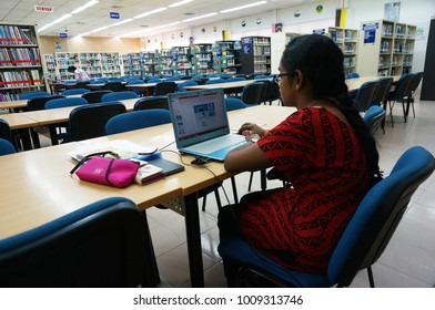 Ipoh, Malaysia - January 23, 2018 : Female Malaysian Indian study in library with laptop on a table in Perak.