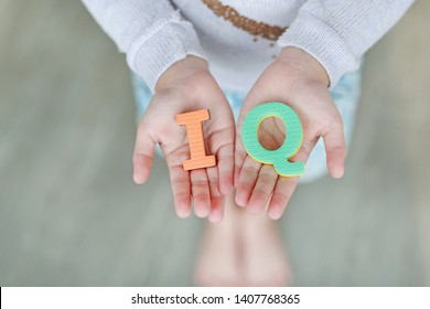 IQ (Intelligence Quotient) sponge text on child hands. Education and development concept.