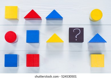 IQ test. Choose correct answer. Logical tasks composed of geometric wooden shapes.  Children's educational logical task, flat lay.