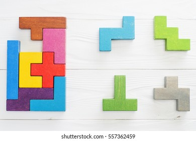 IQ test. Choose correct answer. Logical tasks composed of colorful wooden shapes, top view. Children's educational logical task, flat lay. Visual conundrum, find the missing piece of the proposed.