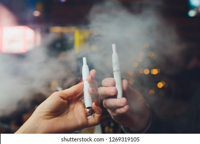 IQOS heat-not-burn tobacco product technology. Man holding e-cigarette in his hand before smoking.