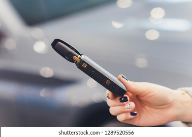 IQOS heat-not-burn tobacco product technology. Woman holding e-cigarette in his hand before smoking.