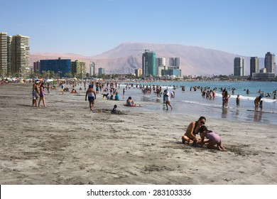 IQUIQUE, CHILE - JANUARY 23, 2015: Unidentified people on the sandy Cavancha beach on January 23, 2015 in Iquique, Chile. Iquique is a popular beach town and free port city in Northern Chile.