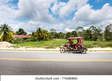IQUITOS, PERU - 11TH JULY 2017: A red mototaxi on the road in a village near Iquitos. Big white clouds in the sky.