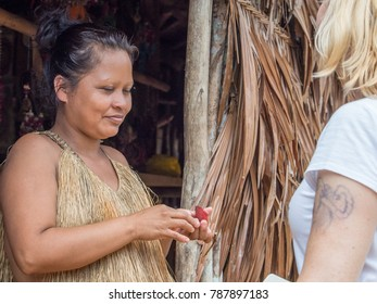 Iquitos, Peru- December 14, 2017: Woman from Yahuas tribe in his local costume. She is puting red line on the face of the tourist.