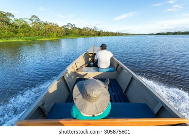 IQUITOS, PERU - MARCH 13: Tourist and guide ride in a boat in the Amazon rain forest near Iquitos, Peru on March 13, 2015