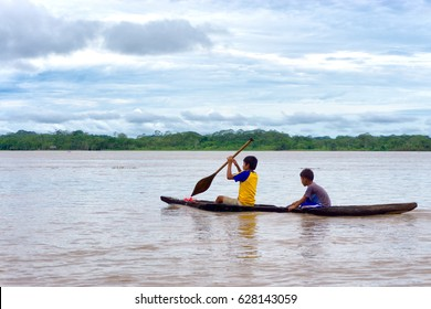 IQUITOS, PERU - MARCH 13: Two children navigate the Amazon River in a dugout canoe near Iquitos, Peru on March 13, 2015