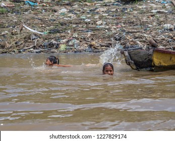 Iquitos, Peru - Sep 25, 2018: Children are swimming and playing  in the  Itaya River. A huge pollution can be seen in the background. Low water season of Amazon. Belén district of Iquitos, Peru