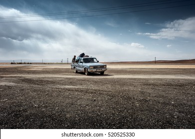 Iran, between Shiraz and Isfahan: Street scene with blue pickup next to the freeway in the middle of the famous Iranian Persian desert - dramatic clouds environment - concept traffic. October 07, 2016