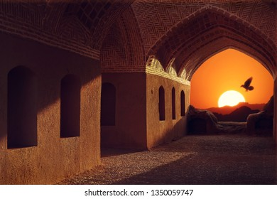 Iran. Yazd. Towers of silence. Sunset and bird on the background of traditional architecture.