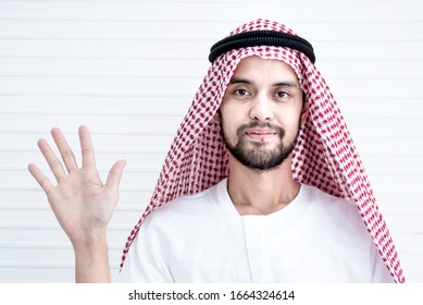 Iranian businessman in traditional muslim dresses showing palm isolated on white background, People sincere emotions, Gesture with his palm on white background,Middle east businessman concept. STOP.