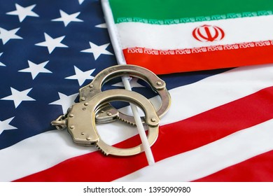 Iranian flag in handcuffs on the background of the American flag. US sanctions against Iran.
