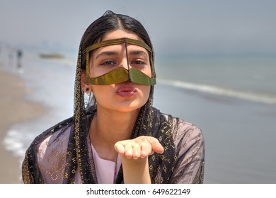 An Iranian girl in a hijab and a traditional mask of Muslims in southern Iran sends an air kiss, Bander Abbas, Hormozgan, Iran, the Persian Gulf coast.
