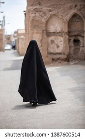 iranian lady, fully covered in her black burqa walking the streets of an old village in Iran