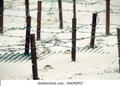 Iraqi anti-personnel mines and barbed wire fences line a beach prior to being cleared in the aftermath of Operation Desert Storm. 1991.