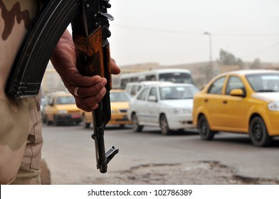 An Iraqi soldier armed with an assault rifle pointed to the ground watching traffic flow by at a roadblock in Baghdad. Narrow DOF, vehicles blurred.