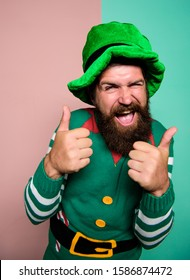 ireland beer tradition. Winter carnival. irish pub party. st patricks day. happy bearded hipster in green hat. christmas elf. happy celebration. cheerful man with beard have fun show thumb up.