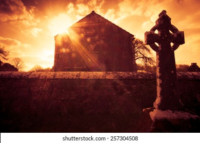 Ireland celtic cross at medieval church cemetery under fiery sky