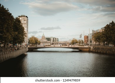 Ireland, Dublin - 18. 09. 2018. Rippled water of river in cityscape with bridge under cloudy sky
