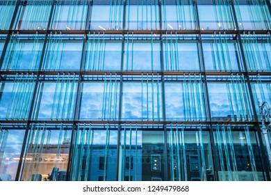 Ireland, Dublin - 18. 09. 2018. Exterior facade of contemporary city building with blue glass reflecting sky in dusk