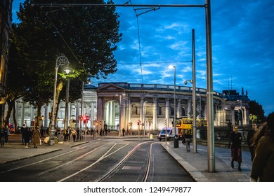 Ireland, Dublin - 18. 09. 2018. Exterior of old city architecture with modern tram riding on road and people walking in twilight