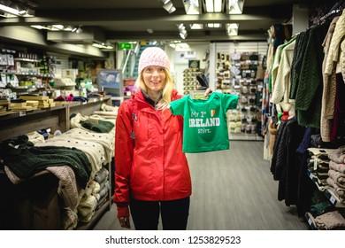 Ireland, Dublin - 19. 09. 2018. Woman in outwear shopping in Irish gift shop holding adorable baby t-shirt
