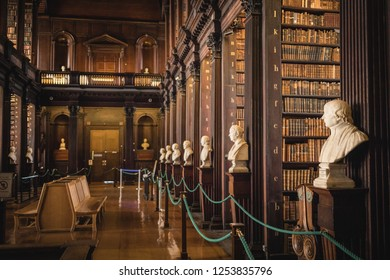 Ireland, Dublin - 19. 09. 2018. Perspective view of hallway in Trinity college library with busts and long wall of old books