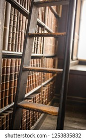 Ireland, Dublin - 19. 09. 2018. Trinity college library with wooden bookshelf full of old books with ladder near