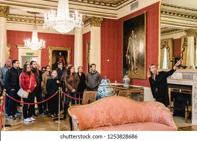 Ireland, Dublin - 20. 09. 2018. Group of tourists in beautiful hall of Dublin Castle listening to guide in bright light of chandelier