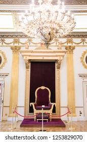 Ireland, Dublin - 20. 09. 2018. Interior of throne hall in Dublin castle with red velvet throne of king under golden chandelier