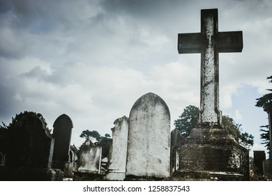 Ireland, Dublin - 21. 09. 2018. Aged gray cross tombstones on Mount Jerome cemetery in dark cloudy day