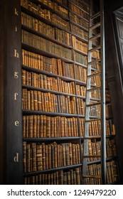 Ireland, Dublin - 29. 09. 2018. Wooden shelves with rows of old books and ladder in library of Trinity college