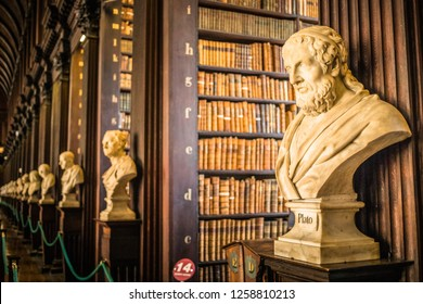 Ireland, Dublin, Trinity College - 29. 09. 2018. Interior of library with wooden shelves full of aged books and busts of ancient Greek personalities