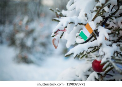 Ireland flag. Christmas background outdoor. Christmas tree covered with snow and decorations and Irish flag. New Year / Christmas holiday greeting card.