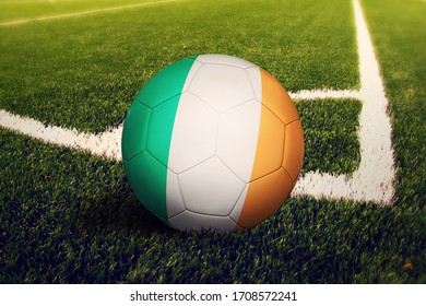 Drapeau d'Irlande sur balle à la position de tir d'angle, arrière-plan football sur terrain. Thème national de football sur l'herbe verte.