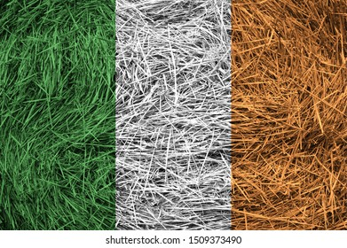 Ireland flag on a hay roll surface. Textured wallpaper background for creativity and design.
