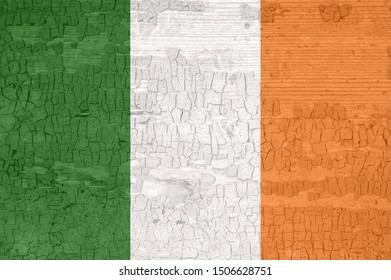Ireland flag on an old painted tattered wooden surface. Textured wallpaper background for design.