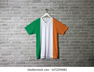 Ireland flag on shirt and hanging on the wall with brick pattern wallpaper, green white and orange.