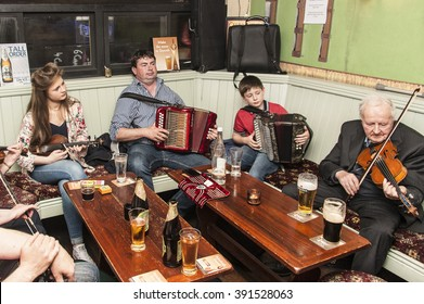 Ireland, Lismore: A group of Irish musicians of all ages old young men women kids female male play Irish Traditionals in a corner of an Irish pub. June 11, 2015