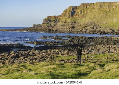 Ireland, MAY 8: Photographer taking picture of the famous ancient volcanic eruption - Giant's Causeway on MAY 8, 2017 at County Antrim, Northern Ireland