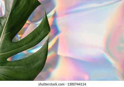 Iridescent background. Holographic Abstract soft pastel colors backdrop with monstera tropic leaf. Minimal concept.