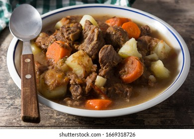Irish beef stew with carrots and potatoes on wooden table