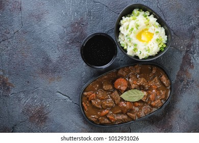 Irish beer and beef stew with champ, traditional dishes for Saint Patrick's Day. Top view on a grey textured background with copyspace, horizontal shot