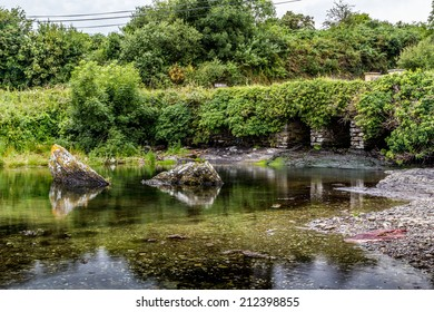 Irish bridge near still water with green foliage in summer