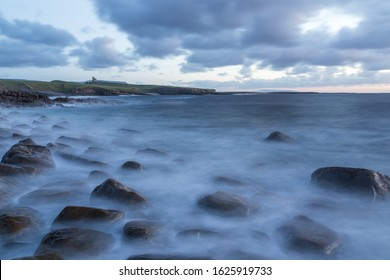 Irish coast and castle with rough ocean and waves