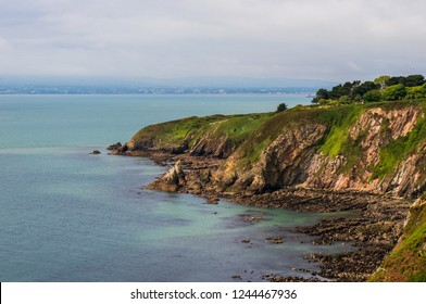 Irish coast landscape with rugged cliffs covered in green grass on a cloudy summer day. Howth Cliff Walk, County Dublin, Ireland.