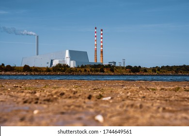Irish coastline in summer with a view of Poolbeg Towers and  beach.he thermal station chimneys are among the tallest structures in Ireland and are visible from most of Dublin city