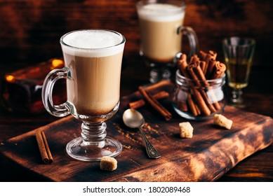 Irish coffee with cinnamon on wooden surface