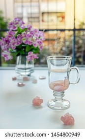 In Irish coffee mug preparing drinkable gem elixir. Burnished rose quartz stones are placed into distilled water. Two stone rabbits sit nearby it. Vase with flowers is seen on the balcony table.