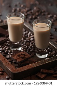 Irish cream baileys liqueur in shot glasses in wooden tray with coffee beans and powder with dark chocolate on dark wood background. Macro